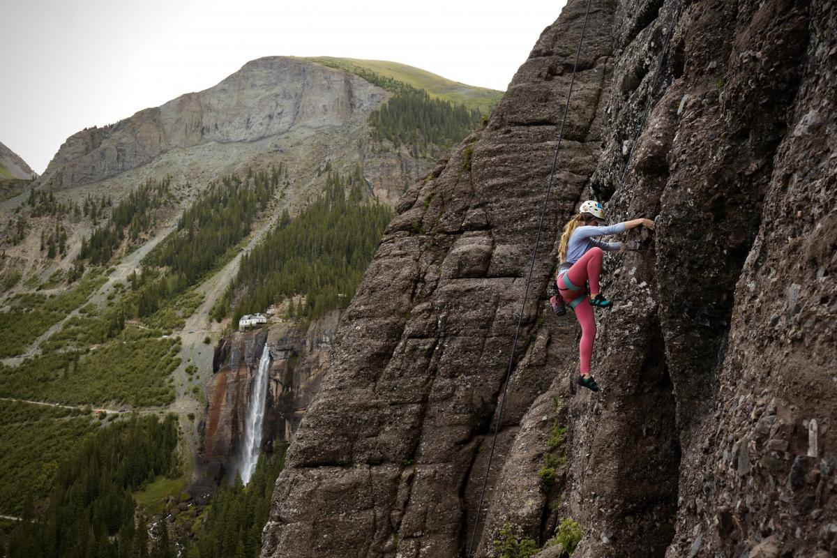 Photo of a person rock climbing by surrounding mountains and waterfall